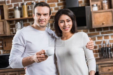 multiethnic couple embracing and smiling at camera while man holding cup of coffee in kitchen