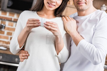 cropped shot of happy man embracing smiling girlfriend holding cup of coffee at home