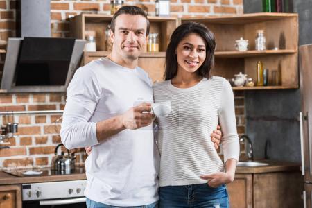 heureux couple multiethnique souriant à la caméra en position debout ensemble dans la cuisine
