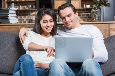 Photo for Happy multiethnic couple using laptop together on couch - Royalty Free Image