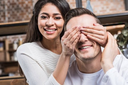 happy young african american woman closing eyes to smiling caucasian boyfriend at home