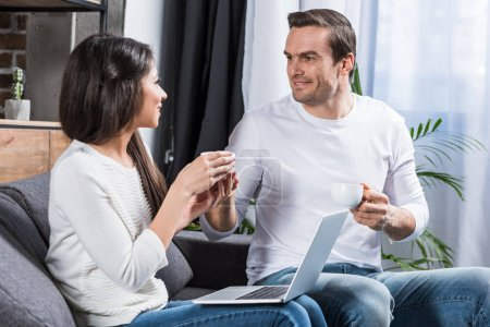 Photo for Couple smiling each other and talking while drinking tea and using laptop at home - Royalty Free Image