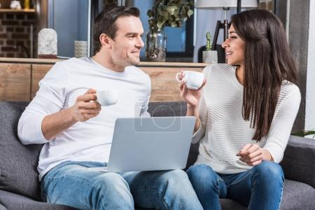 multiethnic couple holding cups of coffee and smiling each other while using laptop at home