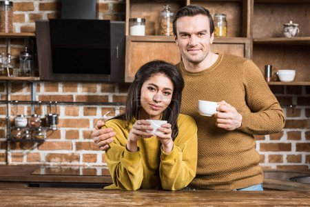Photo for Happy multiethnic couple drinking coffee and smiling at camera in kitchen - Royalty Free Image