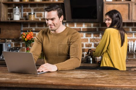 smiling young man using laptop while girlfriend cooking behind in kitchen