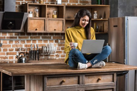smiling african american girl holding coffee cup and using laptop while sitting on wooden table top in kitchen