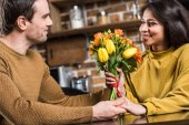 smiling young man presenting beautiful flower bouquet to happy girlfriend at home