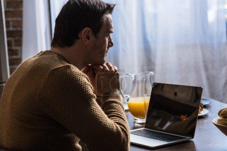 Photo pour Vue latérale de l'homme à l'aide d'ordinateur portable avec écran blanc à la maison - image libre de droit