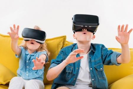 Photo for Excited siblings using virtual reality headset and sitting on yellow sofa - Royalty Free Image