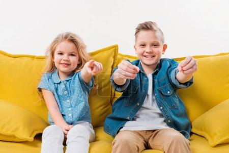 Photo for Little boy driving and sister pointing while sitting on yellow sofa - Royalty Free Image