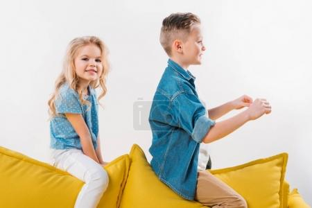 boy pretending to be a driver while sitting on sofa with sister