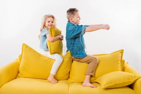 boy pretending to be a driver while sitting on yellow sofa with sister