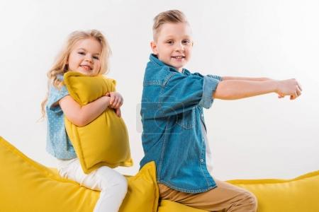 happy boy pretending to be a driver while sitting on yellow sofa with sister