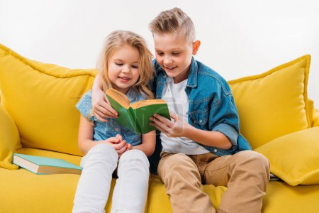 happy siblings reading book and sitting on yellow sofa