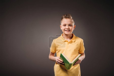 Photo for Preteen boy holding book, isolated on grey - Royalty Free Image