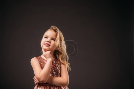 adorable thoughtful child in pink dress, isolated on grey