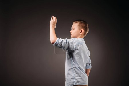 preteen boy holding something, isolated on grey