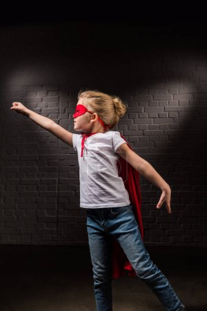 female child flying in red superhero mask and flying