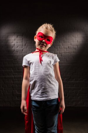 kid in superhero costume with red mask and cloak