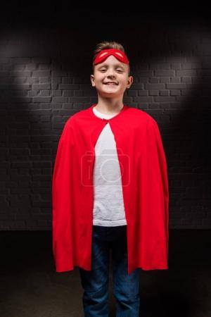 smiling boy in superhero costume and mask