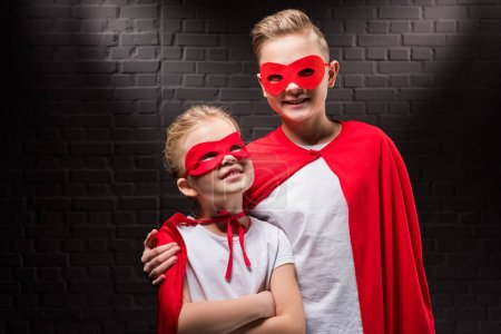 smiling siblings in red superhero costumes and masks