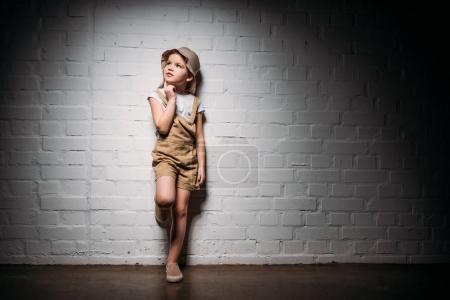 thoughtful female child in safari costume standing at white wall