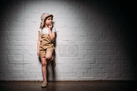 pensive child in safari costume standing at white wall
