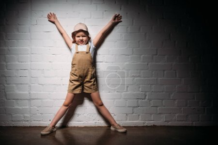 little child in safari costume standing at white wall