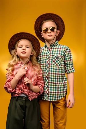 Photo pour Peu élégant Cow-Boy et cow-girl posant dans chapeaux, isolé sur jaune - image libre de droit