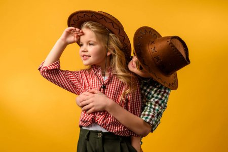 little cowboy embracing stylish cowgirl, isolated on yellow