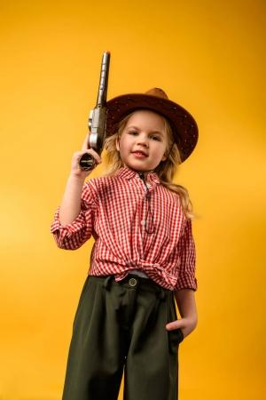 stylish cowgirl in hat with gun, isolated on yellow