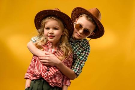 little stylish cowboy and cowgirl in hats hugging isolated on yellow