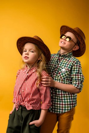 little stylish cowboy and cowgirl in hats, isolated on yellow