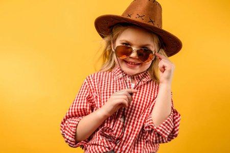 Photo pour Cowgirl chic en chapeau et des lunettes de soleil, isolés sur jaune - image libre de droit