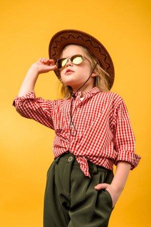 Photo pour Belle cowgirl chic en chapeau et des lunettes de soleil, isolés sur jaune - image libre de droit