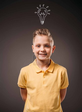 adorable preteen smiling boy with drawn light bulb idea, isolated on grey