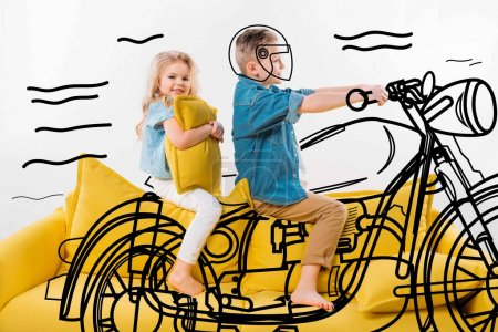 boy pretending to be a biker and riding motorbike while sitting on yellow sofa with sister