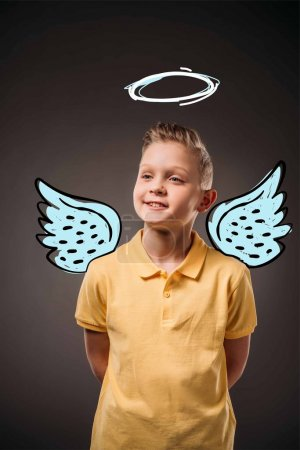 portrait of adorable preteen boy with drawn wings and nimbus as angel, isolated on grey