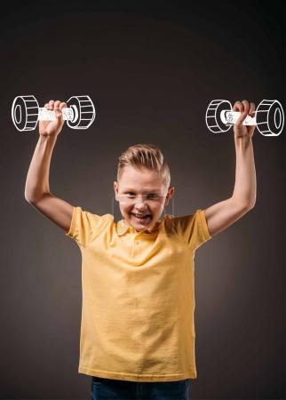 smiling boy pretending to be a sportsman and training with dumbbells, isolated on grey
