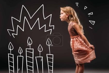 pretty child in pink dress blowing drawn birthday candles, isolated on grey