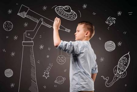 Photo for Preteen boy pretending to be a astronomer with drawn telescope and UFO, planets, spaceship and stars icons - Royalty Free Image