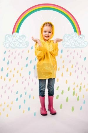 Photo for Little kid in yellow raincoat and rubber boots, with rainy clouds and colorful rainbow illustration - Royalty Free Image