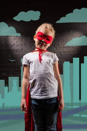 kid in superhero costume with red mask and cloak with city illustration on background