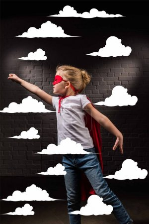 female child flying in red superhero mask and flying in clouds