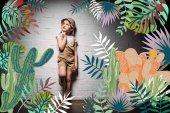 enfant pensif en costume safari debout sur un mur blanc avec une illustration de cactus