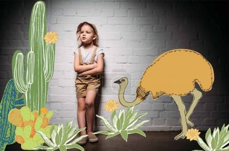 child in safari costume with crossed arms standing at white wall with cactuses and ostrich illustration
