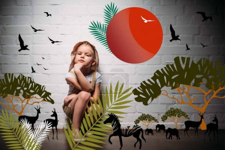 female child in safari costume and hat sitting at white wall with safari animals illustration