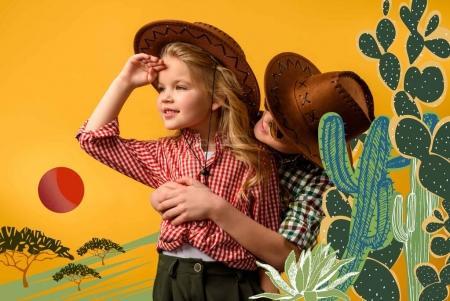 Photo pour Petit cow-boy embrassant cow-girl élégant, isolé sur jaune avec illustration de cactus - image libre de droit