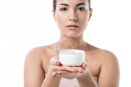 beautiful girl showing moisturizing cream isolated on white