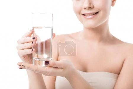 cropped image of beautiful smiling girl holding glass of water isolated on white